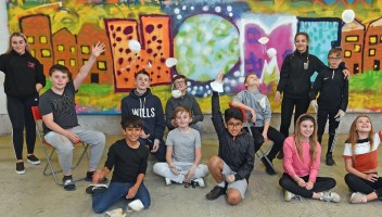 Photo of young people in front of graffiti mural.