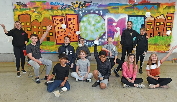 Photo of young people in front of mural.