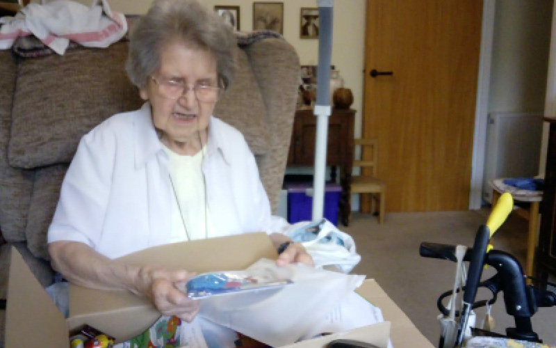 Photo of Pat opening her parcel.