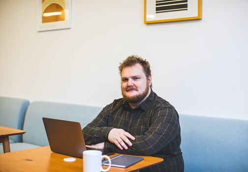 Photo of a man sitting at a laptop.