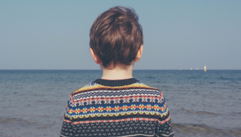 Photo of a child looking out to sea.