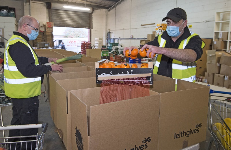 Photo of oranges being added to food hampers.